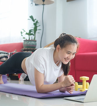 fit-woman-doing-yoga-plank-and-watching-