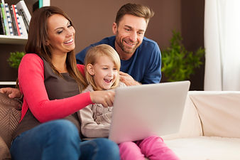family-laughing-together-using-laptop-ho