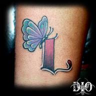 tiny butterfly on letter L on dark skin.