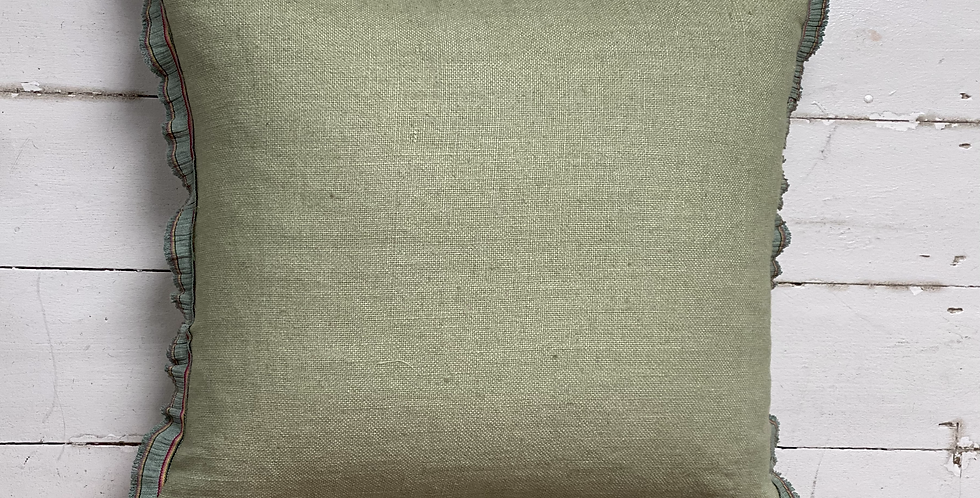 Soft green linen cushion with vintage trim