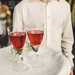 waiter-carries-glasses-with-red-drink-de