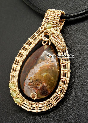 14K gold-fill wire-wrap pendant frame around brown moss agate bead. Frame includes peridot beads and embroidery-style wire-wrap leaf.