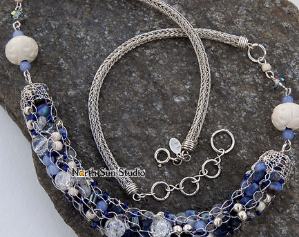 Sterling silver necklace with bead-soup focal in blues and purple. Focal is French-knit with wire-wrap netting end caps, necklace band is double Viking-knit with handmade end caps.