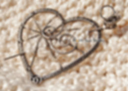 Titanium wire-wrap shawl-pin/brooch. Open-work body: heart with spider web. Pin end has decorative wire-wrap bee/insect.