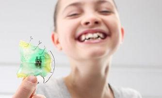 Kind zeigt Zahnspange