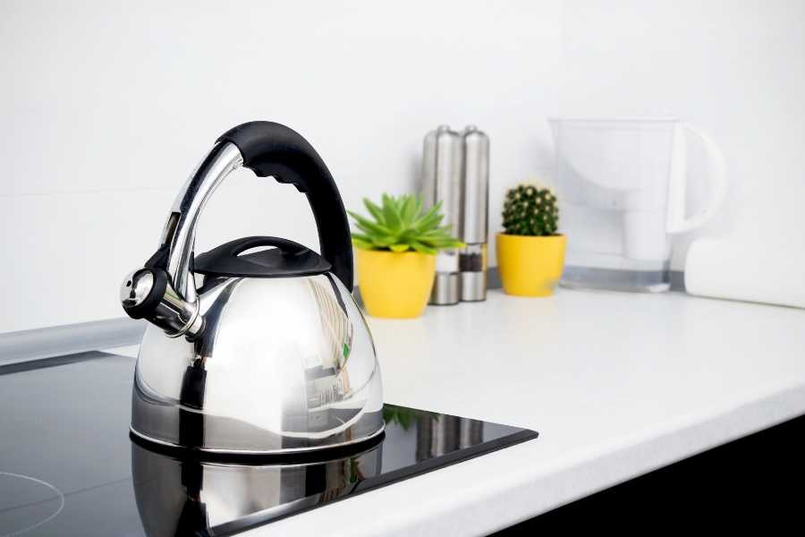 kettle over induction stove in front of white tiles