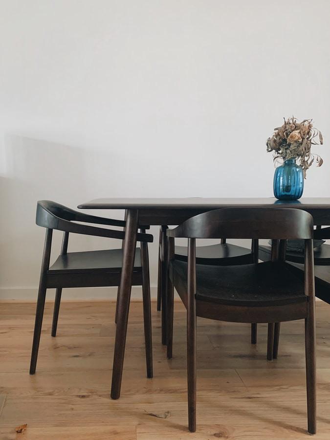 minimalist dark brown dining room with glass flower vase