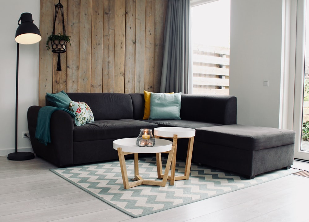 minimalist apartment living room wooden walls and black sofa