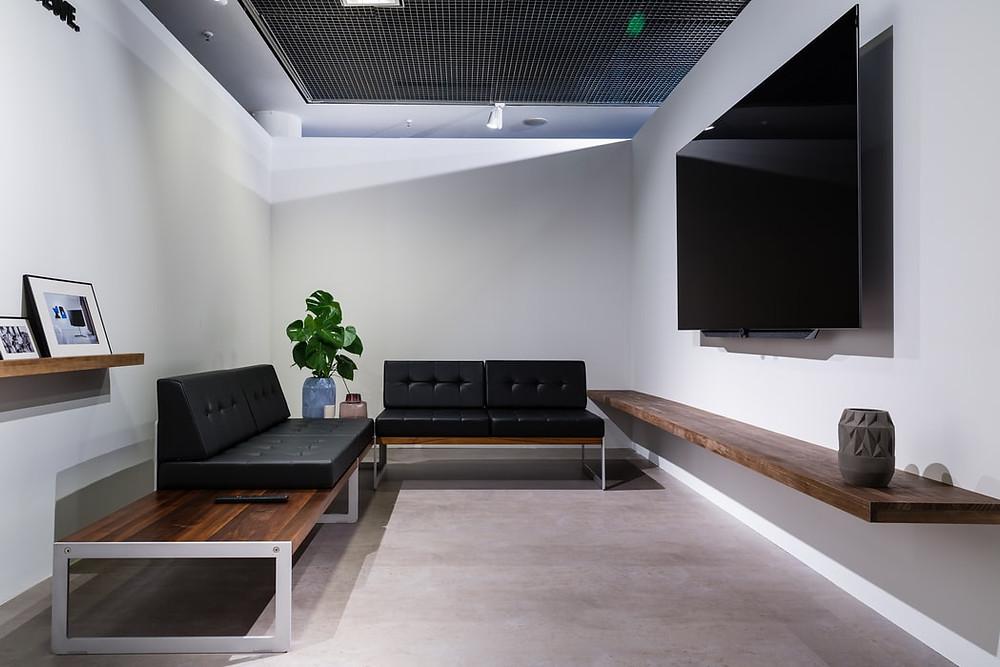 minimalist bachelor living room grey floor and black sofas