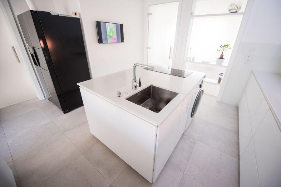 minimalist kitchen white island with sink, stovetop and washing machine