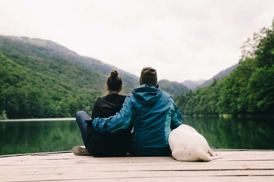 minimalist couple with dog sitting in front a lake