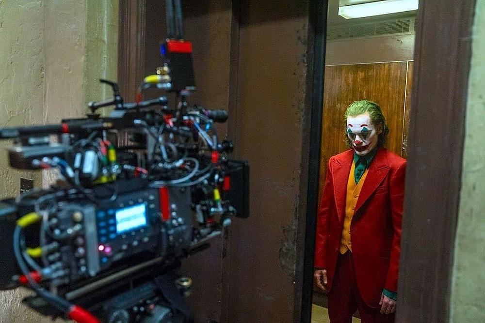 Joaquim Phoenix vestido como Coringa: clazer vermelho, colete laranja, camisa verde, maquiagem de palhaço. Ele se encontra no lado direito da imagem e no lado esquerdo há uma câmera que está gravando a cena.