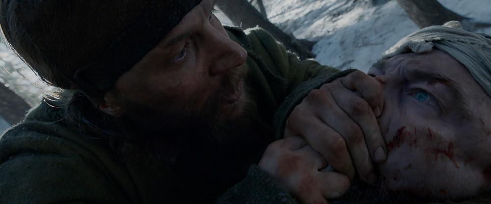 Um homem tapa a boca de outro que parece estar deitado no chão. Ambos estão bastante sujos e com escoriações no rosto. Há neve no cenário.