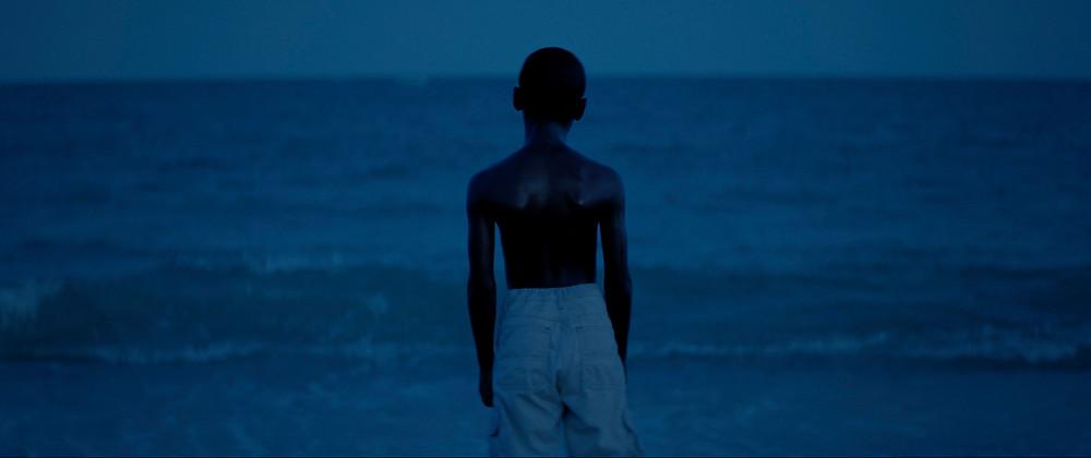 Garoto de costas olhando para o mar. Luz azul predomina sobre a cena.