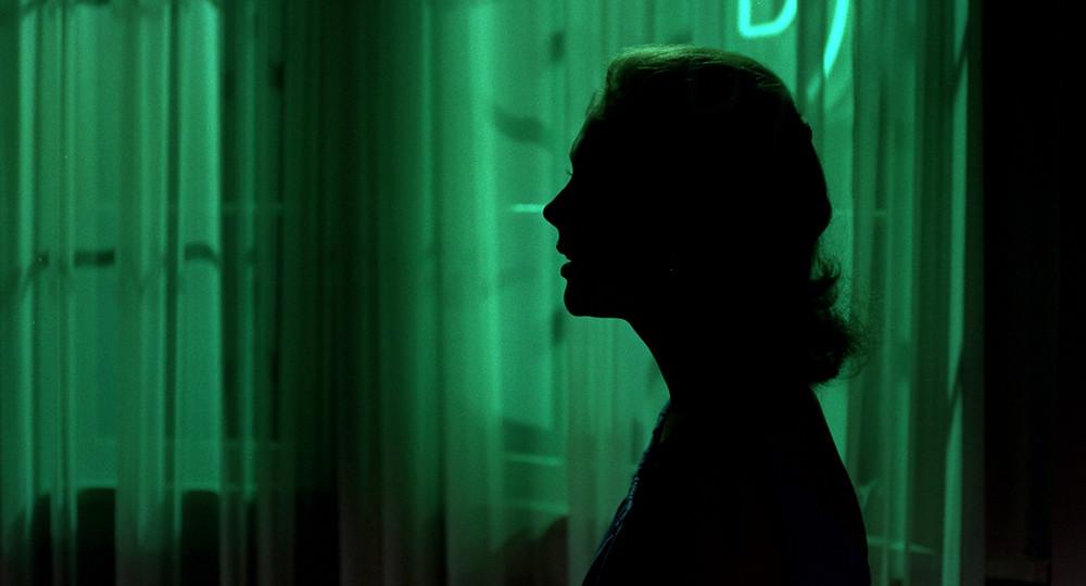 Silhueta de uma mulher de perfil em frente a cortinas que rebatem uma luz verde.