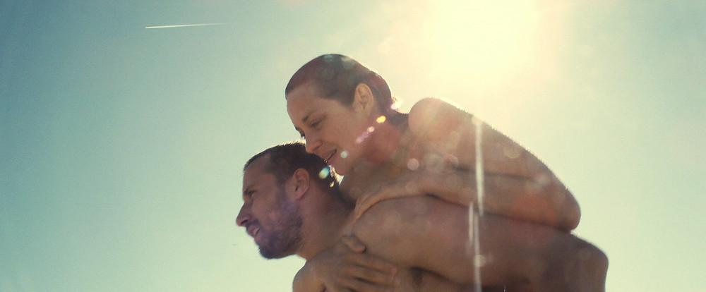 Homem segurando uma mulher nas costas, os dois semi-nus. Tudo que se vê é o raio de sol e o céu, além das personagens.