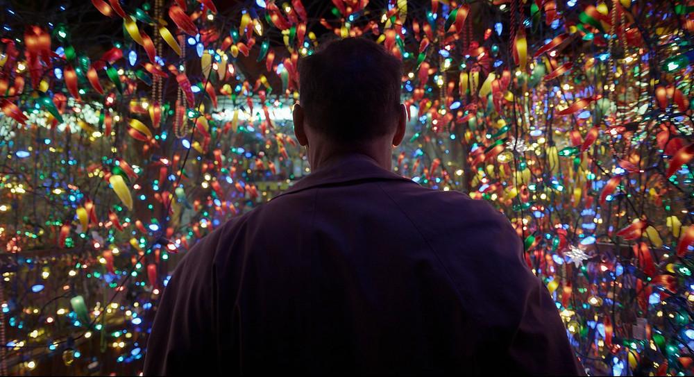 Homem andando no meio de luzes coloridas. Não é possível ver seu rosto, uma vez que a câmera o segue atrás.