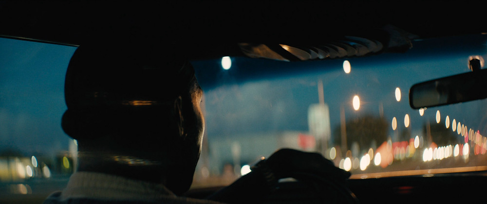 Homem dirigindo um carro à noite e as luzes da cidade são vistas além.