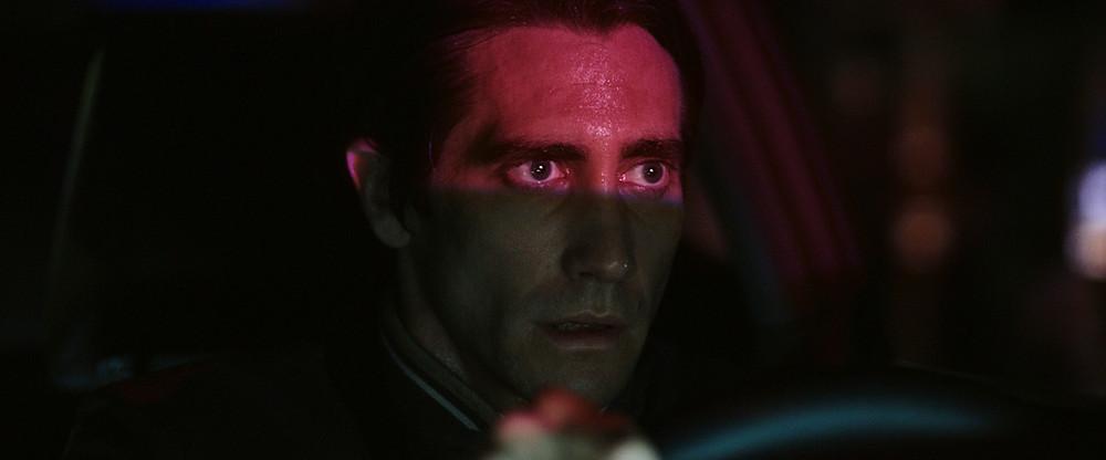 Homem olhando para um ponto fixo além da câmera com uma luz rosa refletindo em seu rosto acima da altura do nariz.