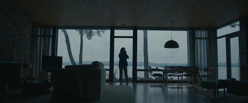 Silhueta de uma mulher segurando um bebê na sala escura com as luzes apagadas olhando para o exterior que é um lago e montanhas azuis.
