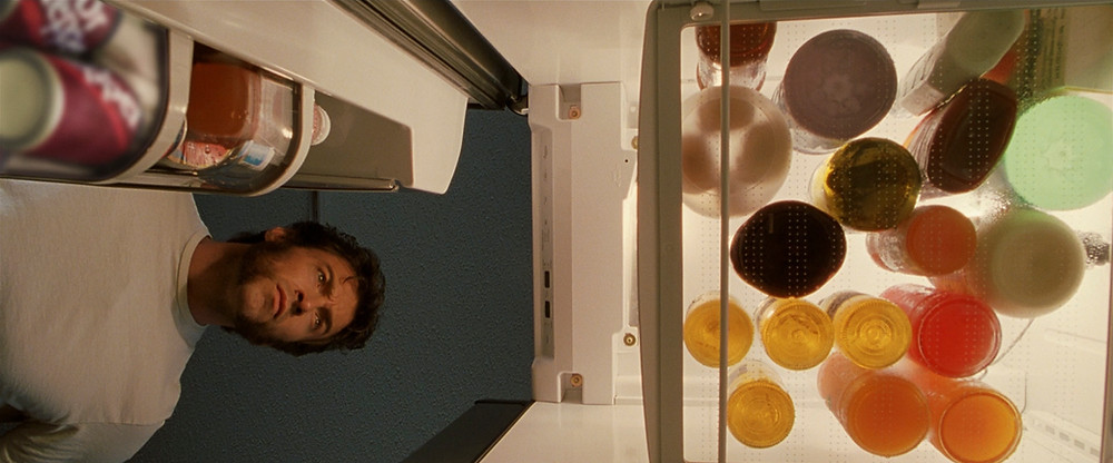 O interior de uma geladeira com vasilhame redondo visto de baixo para cima e o Wolwerine segurando a porta aberta enquanto olha para dentro.
