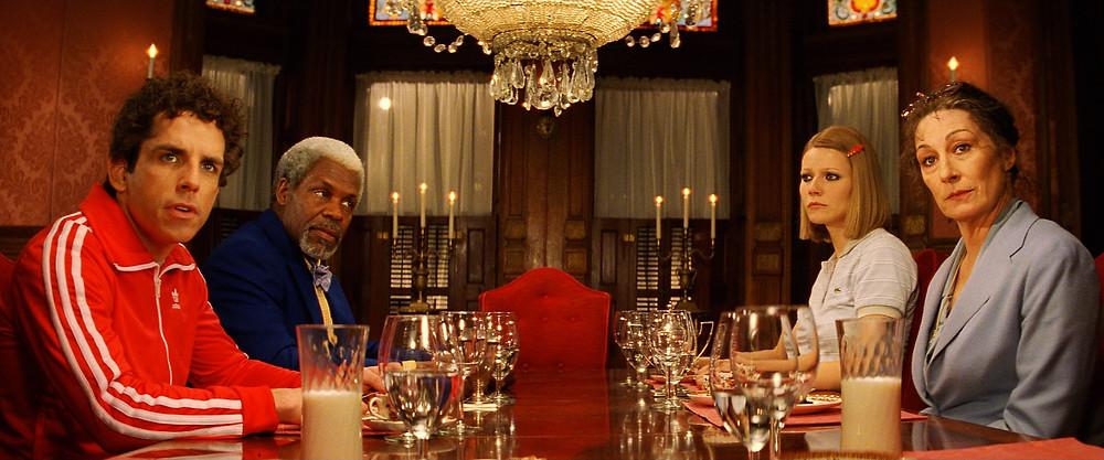 Quatro personagens sentados à mesa de jantar em uma sala luxuosa, com muitos cristais e a cor vermelha prevalesce.