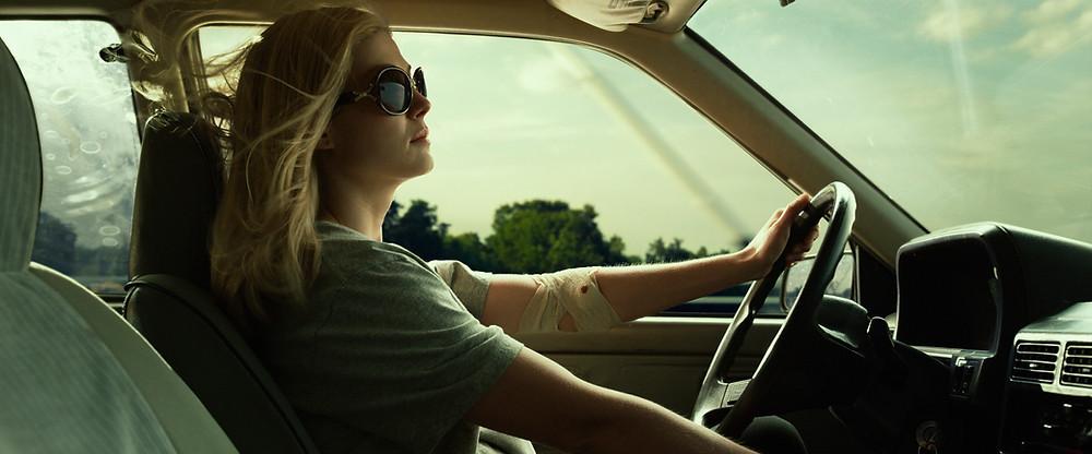 Mulher de perfil dirigindo um carro com o braço enfaixado e uma pequena marca de sangue. O carro está em movimento e seus cabelos ao vento.