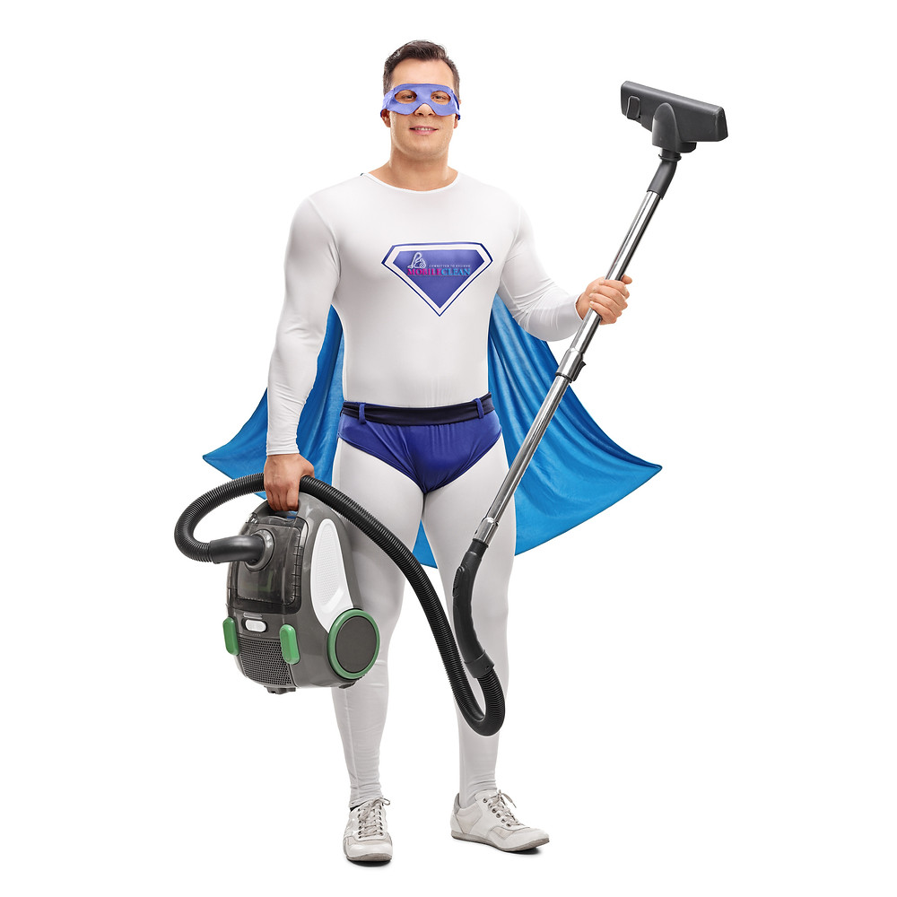 A man in a superman outfit and mask carrying a hoover