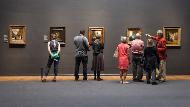 Guests admiring Flemish works of art inside the Rijksmuseum