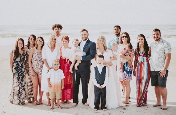 A wedding party in an array of maxi dresses, rompers, khaki shorts and short-sleeve button up shirts stands on the beach.