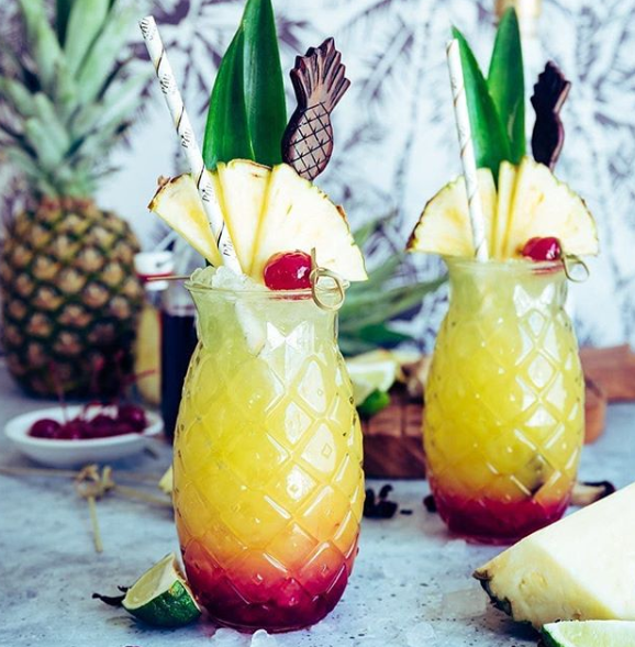 Two pineapple cocktails in pineapple shaped glasses with paper straws