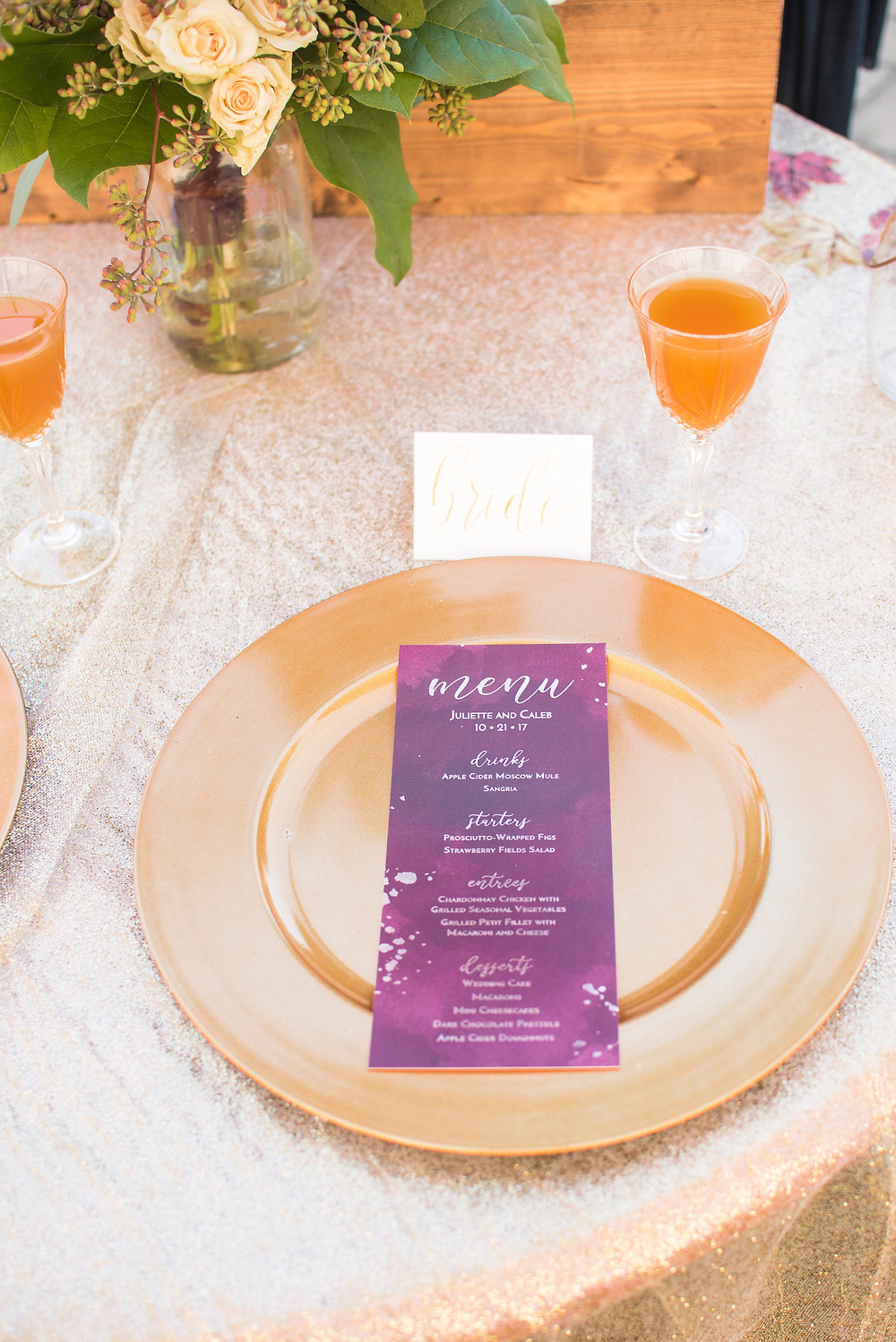 A place setting with a charger, menu, bouquet, and glass of sangria.