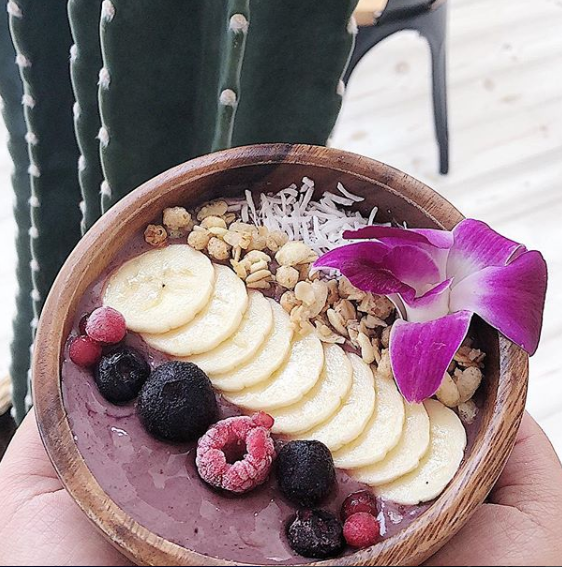 An acai bowl with bananas, berries, coconut, granola, and a flower.