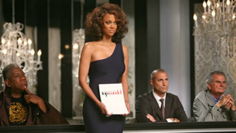 Tyra Banks on America's Next Top Model holding the photos of the models who have made it to the next round.
