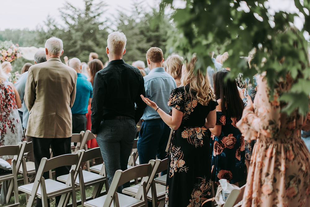 Guests standing at their seats at a wedding