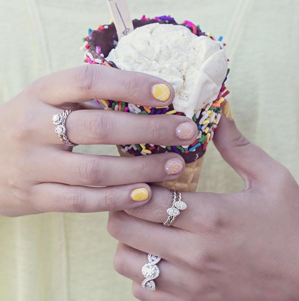 A woman wearing rings holds a waffle cone dipped in chocolate and sprinkles filled with vanilla ice cream.