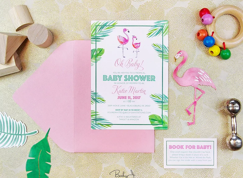 A baby shower invitation with flamingos and tropical leaves on it.