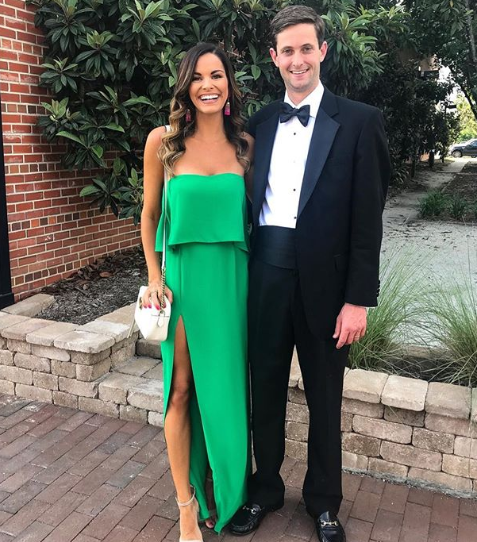 A smiling woman in a long, strapless dress with a slit stands next to a man in a tuxedo with a black bowtie at a wedding.