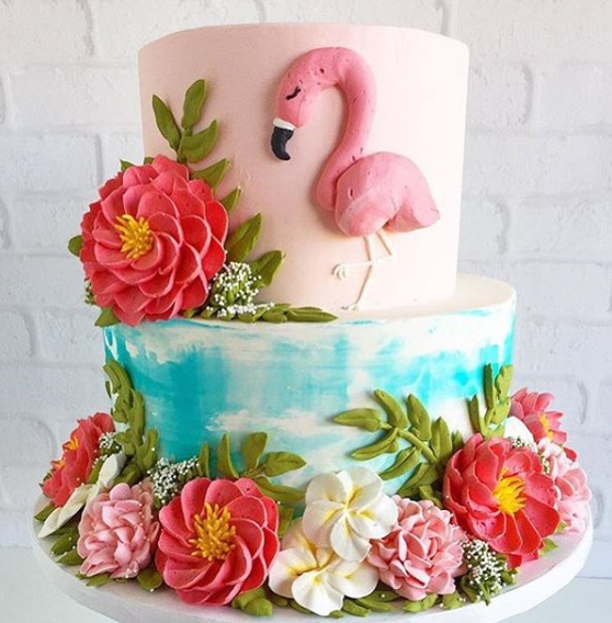 A three tier cake with flowers and a flamingo on it.