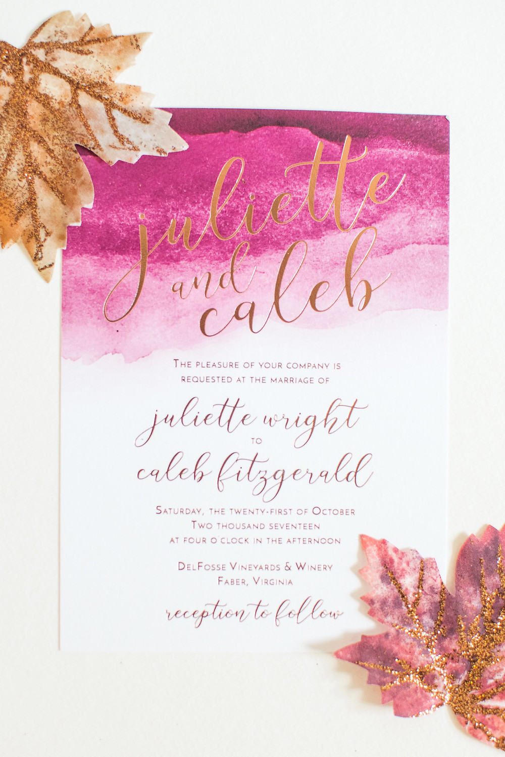 A wedding invitation with some fall leaves.