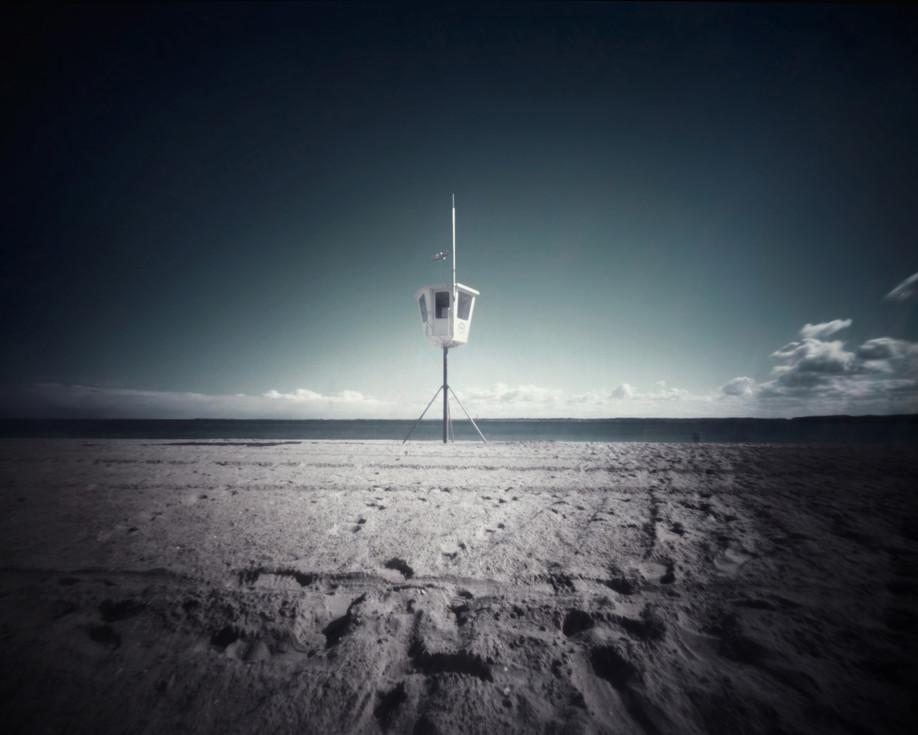 Ein Turm der Rettungswacht erhebt sich einsam in den Himmel. Er erinnert an Sommer, an flirrende Hitze und menschenvolle Strände. Als hätte sie meine Gedanken, die Sehnsucht nach Wärme vernommen, bricht die Sonne zwischen Wolkenfetzen hervor und taucht mein Gesicht in goldene Strahlen. Zeitraffer, als sich türmende Wolkenberge über das Meer hinweg ziehen und den Himmel in klarer Farbe zurücklassen. Die dunklen Stunden sind für den Moment vergangen, der feuchte Sand lechzt nach Wärme und beginnt sich langsam unter meinen Füßen zu lösen.