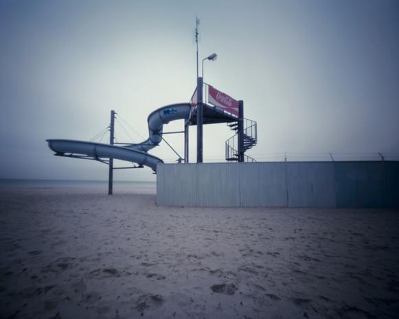 Schritte im Sand tragen mich weiter. Die große Rutsche verliert sich in der Weite des Strandes und des ewigen Horizontes. Fast ist mir, als höre ich Kinderlachen, Stimmengewirr aus der Ferne, welches sich aufbäumt und von den Stunden unbeschwerter Sommertage erzählt, ehe es sich wieder im winterlichen Wind verliert. Wir beide, zwei einsame Gestalten.