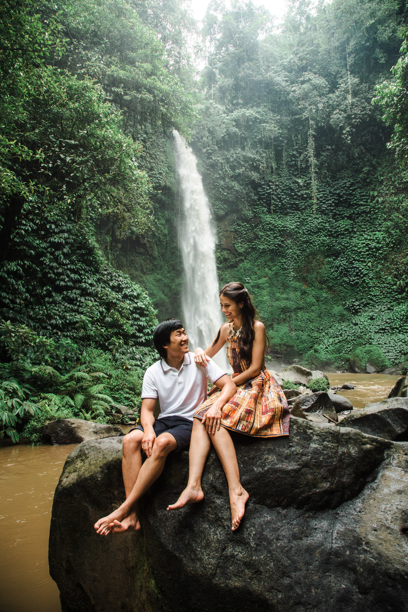 Lovers sit on a stone near waterfall