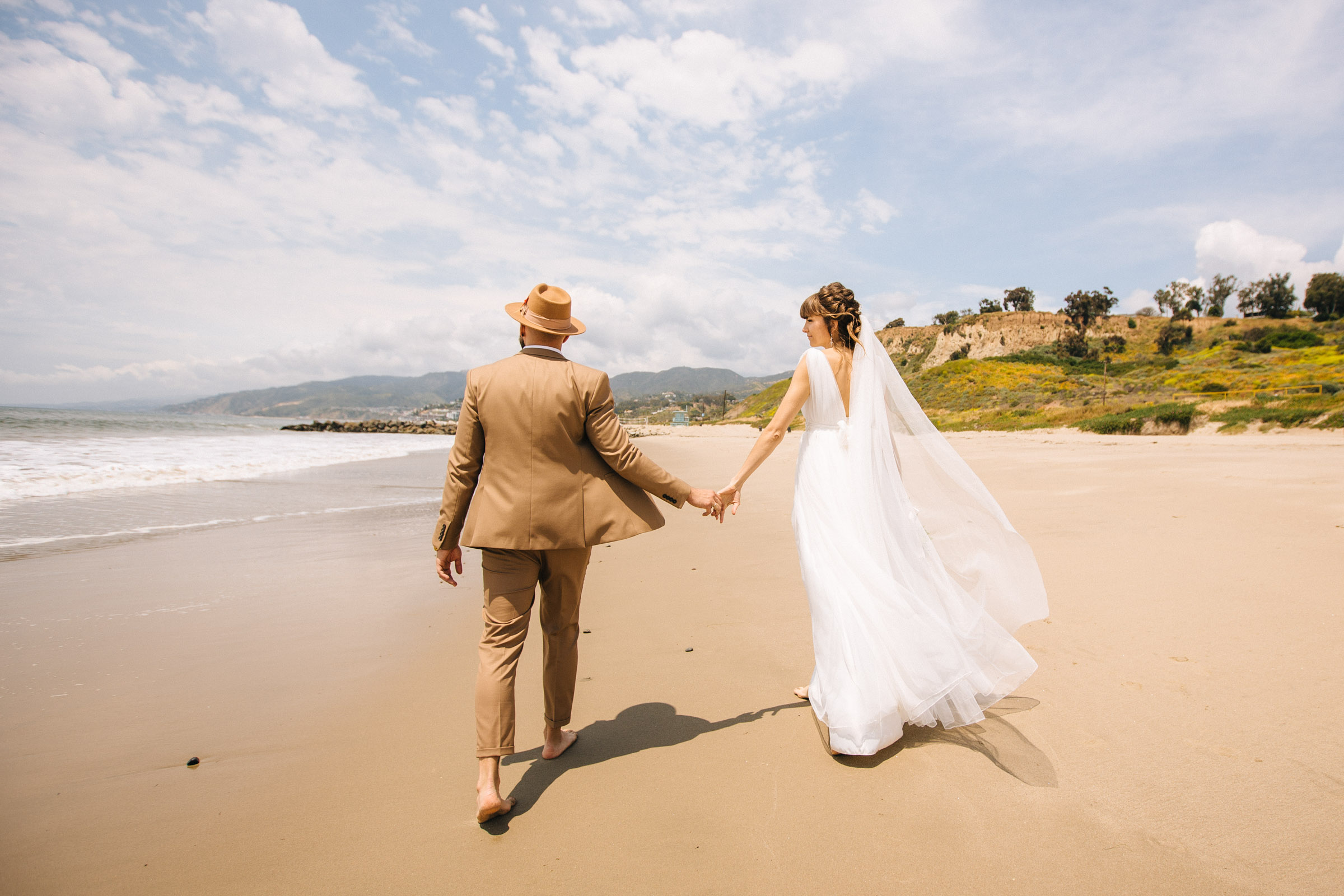 Newlyweds walking along the beach holdin