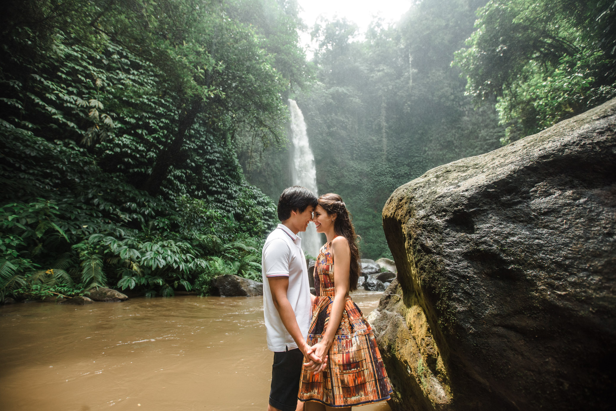 Lovers hold hands at the waterfall