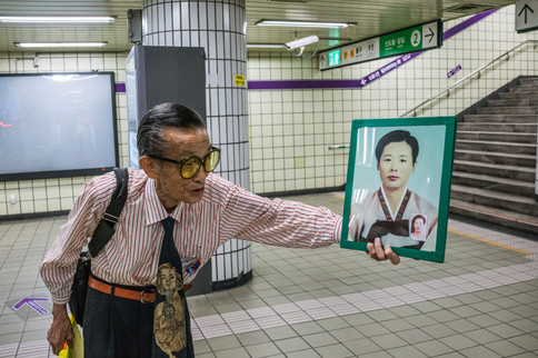 Old Man Holds a Picture of His Wife