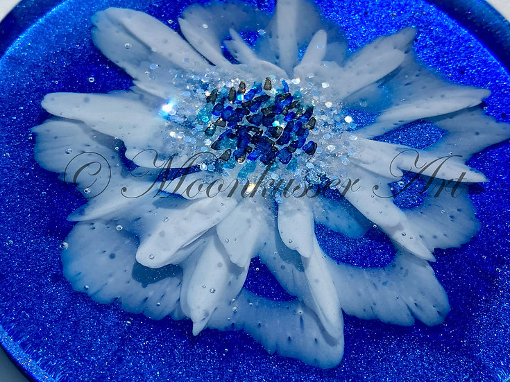 Resin Art Coasters - Dahlia on Blue, white resin flower with sparkling center floats over blue background