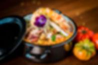 Foodfotografie Gastronomie Restaurant Fotografie Aufnahme eine Pfanne mit Risotto und Crevetten daneben Tomaten und Blumen als Dekoration, Werbeaufnahme