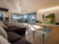 Immobilien und Architektur Fotografie, Wohnzimmer mit Sofa, TV und HiFi Anlage fotografiert mit Sonneneinfall. Grün braune Einrichtung, Echtholzparkett