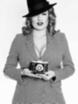 Zoe Scarlett schweizer PinUp Starlet und Bourlesque Tänzerin mit einem schwarz weiss kariertem Blazer und einer Kamera in der Hand, fotografiert im Schweizerhof Luzern